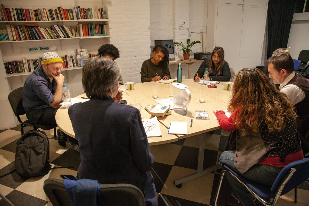 people sitting round a table at a creative writing workshop